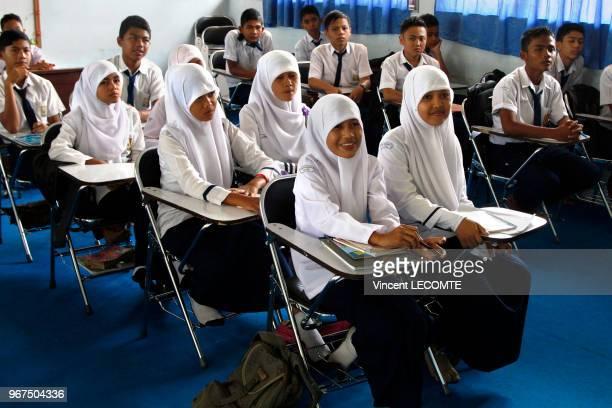 Intérieur dune classe où lycéens et lycéennes musulmans vêtus de luniforme scolaire indonésien exigeant le port du voile par les filles suivent un...