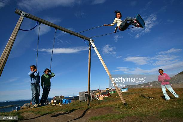 Inuit children play on the swings August 28 in the village of Ilimanaq Greenland Even though the disappearing ice cap could lead to higher sea levels...
