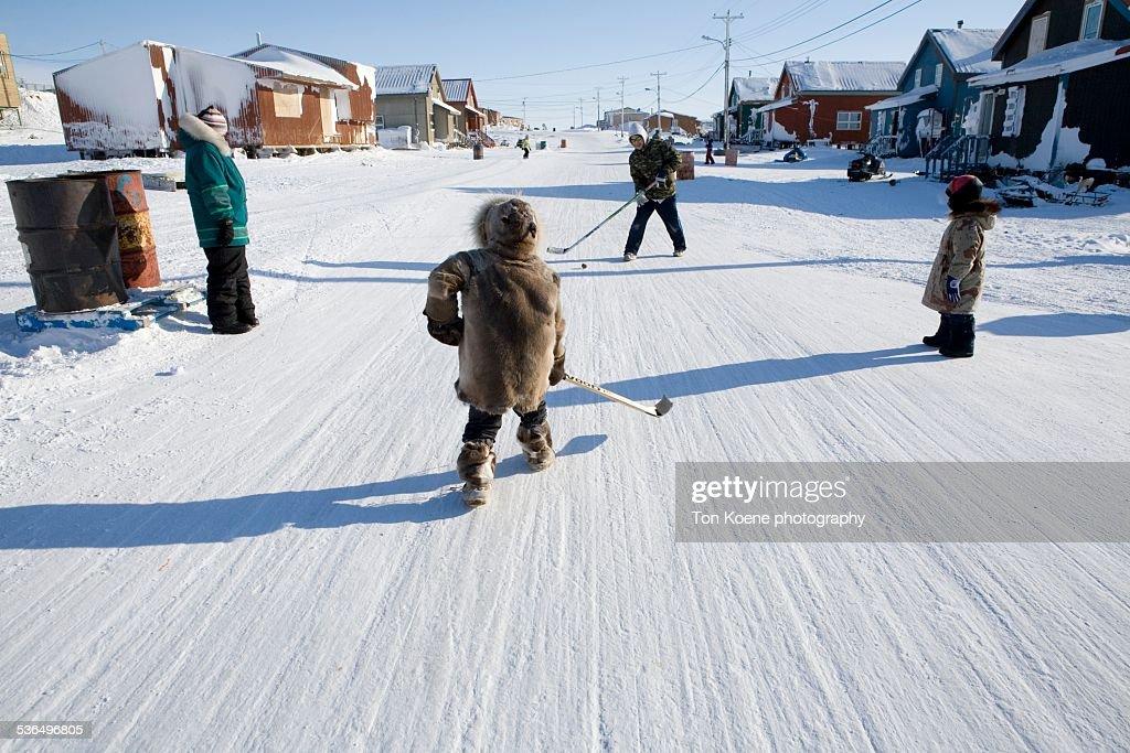 Inuit children playing ice hockey : Foto stock