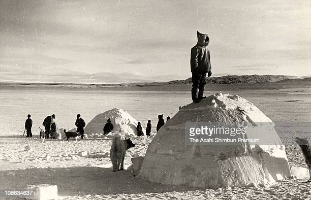 Inuit children stand on an igloo in May 1963 in Canada