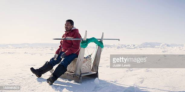 Inuit fisherman rests on sled while ice fishing
