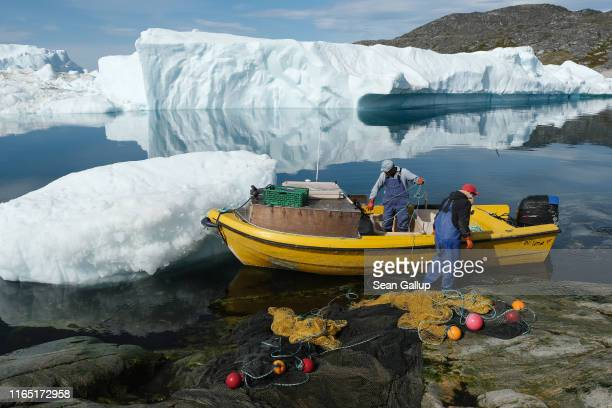 Inuit fishermen prepare a net as free-floating ice floats behind at the mouth of the Ilulissat Icefjord during unseasonably warm weather on July 30,...