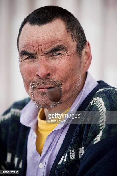 inuit hunter portrait - smiles and smokes pipe - inuit stock-fotos und bilder
