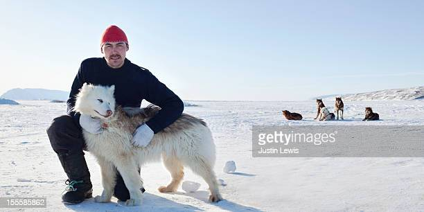 inuit man poses with arctic dog on sea ice - inuit stock pictures, royalty-free photos & images