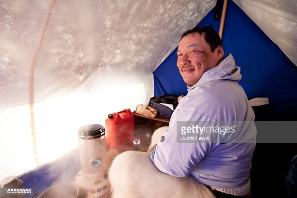 inuit man smiles inside tent while camped on ice - inuit stock pictures, royalty-free photos & images