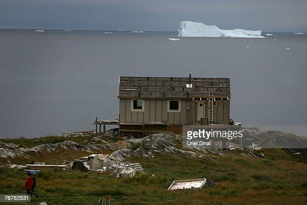 Inuit pass by a house under construction August 26 2007 in the Greenland village of Ilimanaq The locals still remembers the last time the sea around...