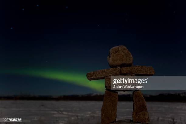 Inuit stone man, inukshuk, stone landmark or cairn, green Northern Lights, Polar Lights (Aurora borealis), near Whitehorse, Yukon Territory, Canada