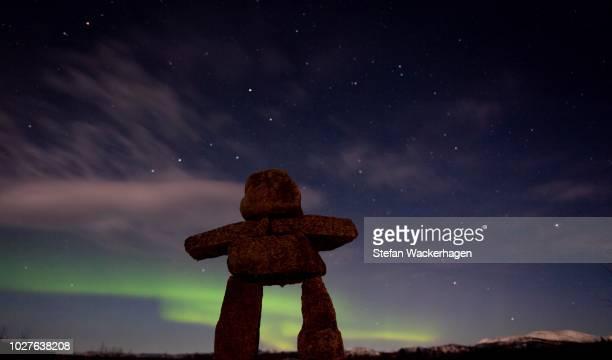 Inuit stone man, inukshuk, stone landmark or cairn, Northern Polar Lights, Aurora Borealis, green, near Whitehorse, Yukon Territory, Canada