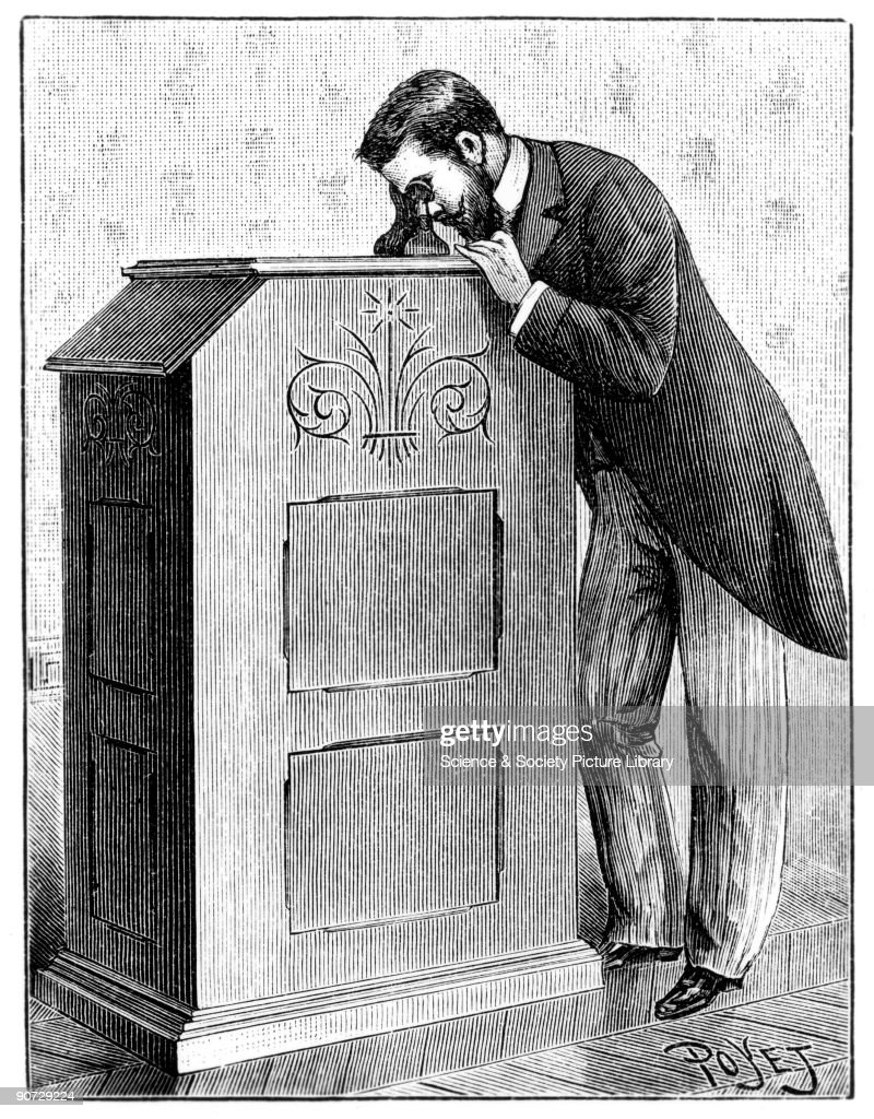 Man using an Edison Kinetoscope, c 1894. Pictures   Getty Images for Kinetoscope Thomas Edison  157uhy
