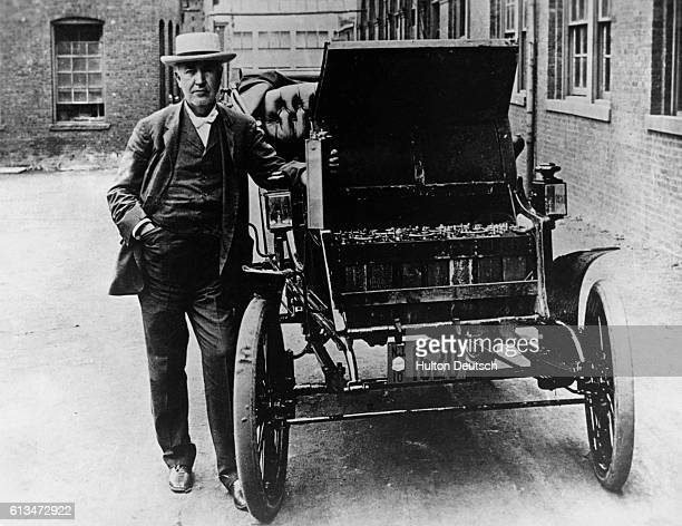 Inventor and physicist Thomas A Edison stands next to his American Barker electric car circa 1895