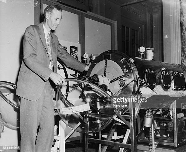 Inventor John Haven Emerson illustrating how his 'Iron Lung' works as Miss Clare Cockerill lies inside the contraption at the WaldorfAstoria...
