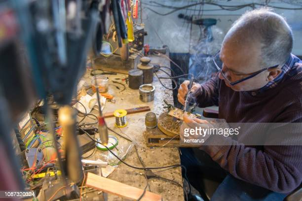 inventor man solldering electronic circuit board - computer motherboard - repairing - inventor stock pictures, royalty-free photos & images