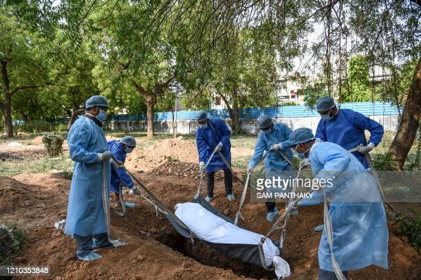 TOPSHOT Inventor Mohammed Sharif Kakuwala with other volunteers wearing protective gear lower a dummy dead body lying on a stretcher with straps to...