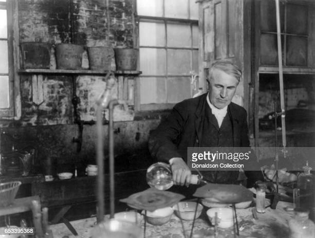 Inventor Thomas Edison pouring a liquid while experimenting in his labratory in 1905 in Orange, New Jersey.