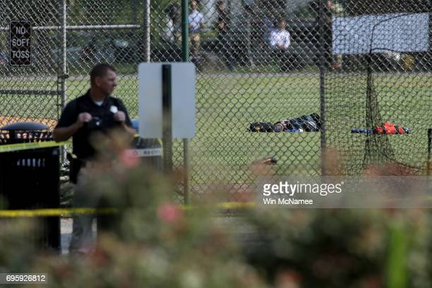Investigators and emergency personnel gather at Eugene Simpson Field the site where a gunman opened fire June 14 2017 in Alexandria Virginia Multiple...