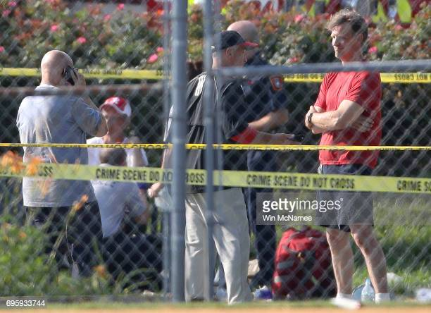 Investigators and men dressed in baseball gear gather at Eugene Simpson Field the site where a gunman opened fire June 14 2017 in Alexandria Virginia...