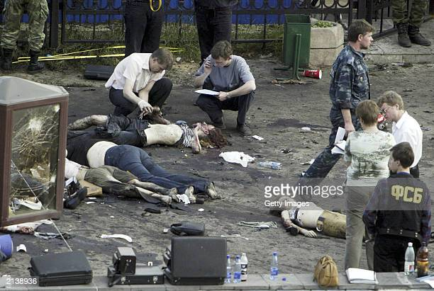 Investigators and police officers examine the bodies of victims near Tushino airfield where a Moscow rock festival was held on July 5 2003 in Moscow...