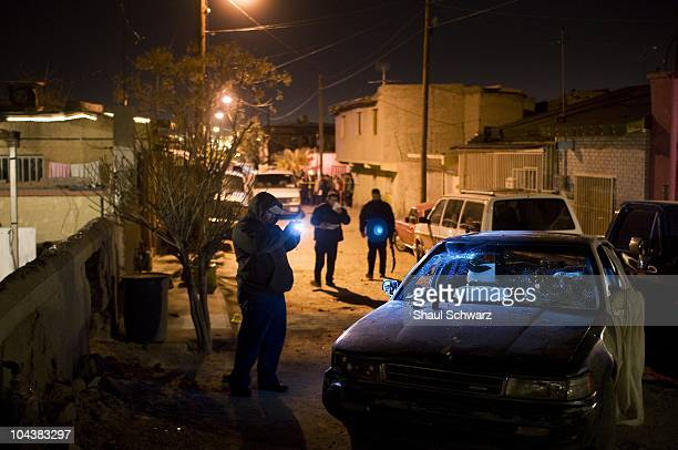 Investigators and Policemen investigate the scene where drug related homicide occured. The death industry is booming in the city of Juarez. Since...