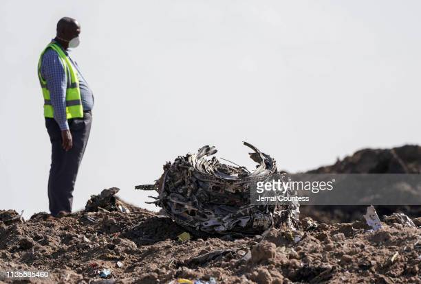 Investigators and recovery workers inspect a second engine after it is recovered from a crater at scene of the Ethiopian Airlines Flight 302 crash on...