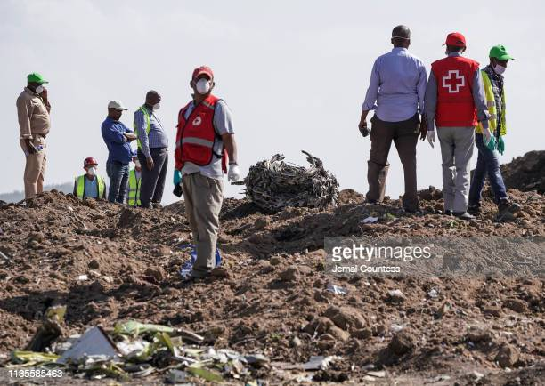 Investigators and recovery workers inspect a second engine after it is recovered from a crater at the scene of the Ethiopian Airlines Flight 302...