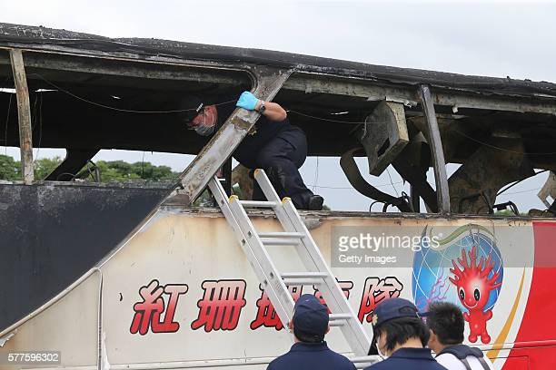 Investigators and rescuers work around the wreckage of a damaged bus as the bus carrying tourists from mainland China crashed and caught fire along...