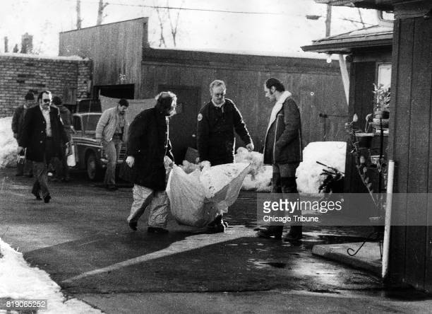 Investigators carry the remains of a body found beneath the garage floor of the home of John Wayne Gacy on December 22 in Chicago