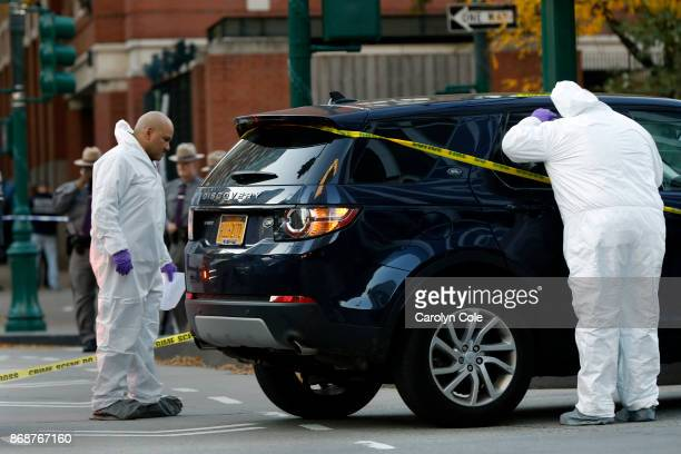 Investigators check a car on West Side Highway near the scene where a truck plowed through a bike path in lower Manhattan on October 31 2017 in New...