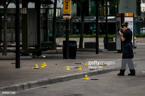 Investigators document the crime scene outside El Centro College where a sniper unleashed a barrage of bullets killing 5 police officers and wounding...