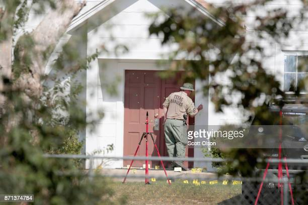 Investigators examine bullet holes in the front door of the First Baptist Church of Sutherland Springs on November 7 2017 in Sutherland Springs Texas...