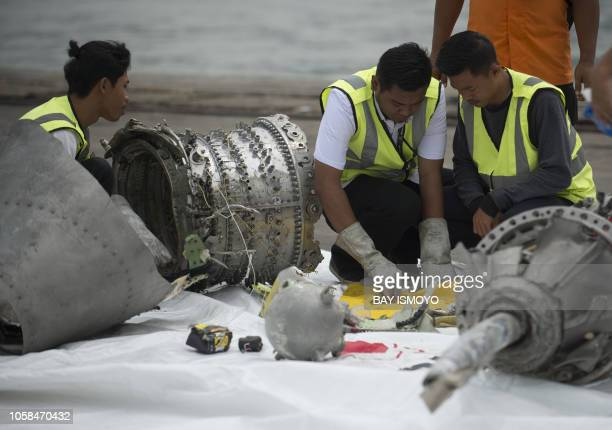 TOPSHOT Investigators examine engine parts from the illfated Lion Air flight JT 610 at a port in Jakarta on November 7 after they were recovered from...