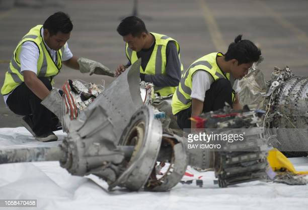Investigators examine engine parts from the illfated Lion Air flight JT 610 at a port in Jakarta on November 7 after they were recovered from the...