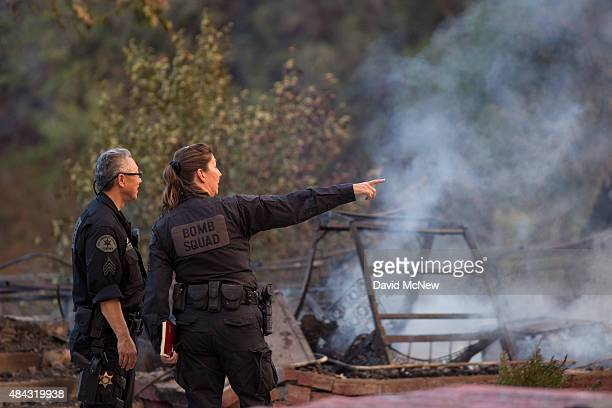 Investigators from the Los Angeles County Sheriff Bomb Squad discuss a possible crime scene among burned buildings at the Warm Springs Rehabilitation...