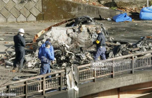 Investigators inspect on Nov 9 the wreckage of a helicopter that crashed a day earlier in the village of Ueno in Gunma Prefecture northwest of Tokyo...