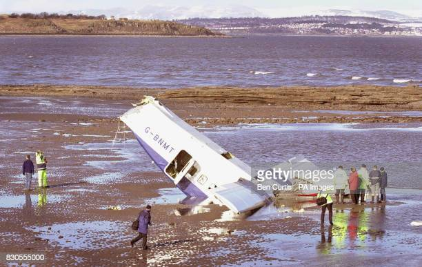 Investigators inspecting the scene as low tide reveals the main section of the 20seater Loganair Shorts 360 light aircraft that crashed into the...