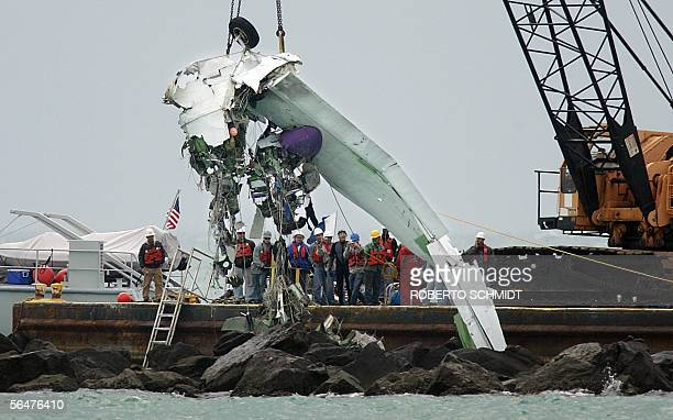 Investigators look at a portion of a wing and wheel well from a Grumman G73T Turbine Mallard a twinengine amphibious aircraft as it is lifted from a...