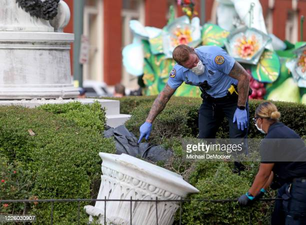Investigators look at the downed statue as New Orleans Police investigate the scene after the statue of slaveholder John McDonough was pulled from...