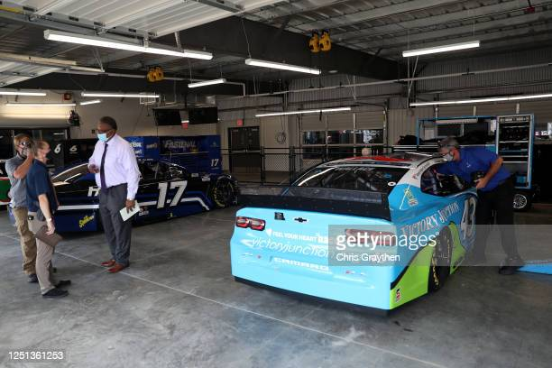 Investigators look on from the garage area of Bubba Wallace driver of the Victory Junction Chevrolet prior to the NASCAR Cup Series GEICO 500 at...