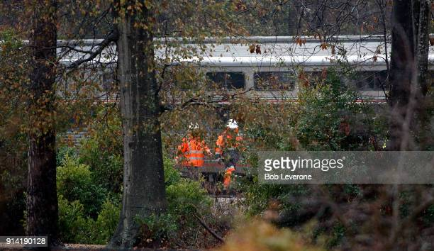 Investigators make their way around the train wreckage under the Charleston Highway overpass where two trains collided early Sunday morning on...