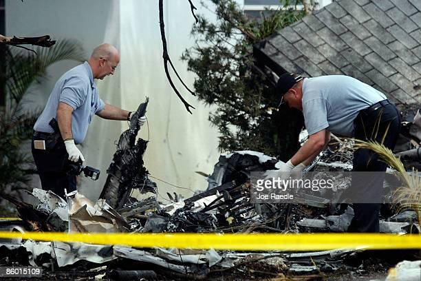 Investigators pick through the wreckage of the Cessna 421 twinengine propeller plane that crashed into a home shortly after takeoff from Fort...