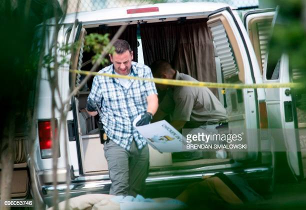 Investigators remove a 'Chicken in Chief' sign from a shooting suspects vehicle after a shooting during a practice of the Republican congressional...