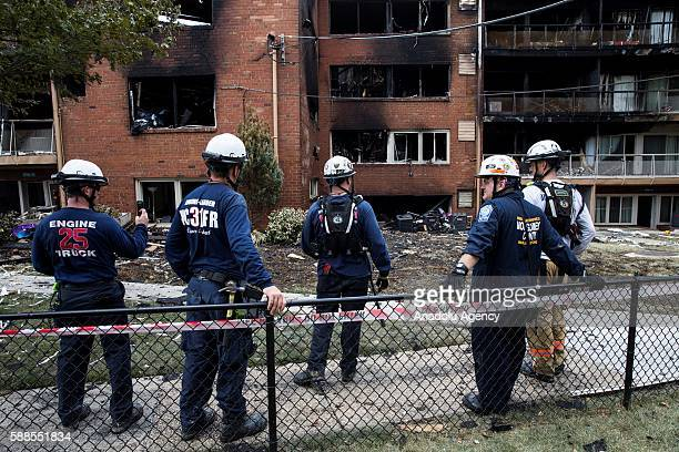 Investigators search through the remains of an apartment building where an early morning blast collapsed part of it and engulfed the rest in flames...