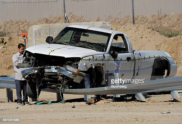 Investigators survey the damage on a pickup truck after it hit the end of a guardrail head on during a slight angle crash test at Karco Engineering...
