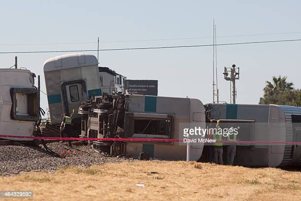 Investigators survey the wreckage of a Los Angelesbound Metrolink train that derailed in a fiery collision with a truck on the tracks on February 24...