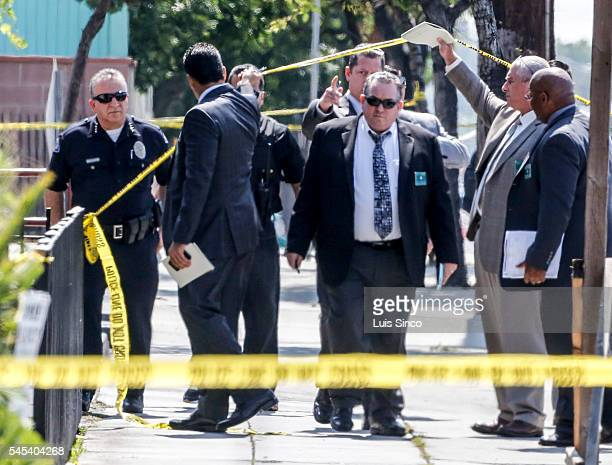 Investigators walk down Florence Avenue after a male domestic violence was shot by three Bell police officers in front of a 7Eleven store at Florence...