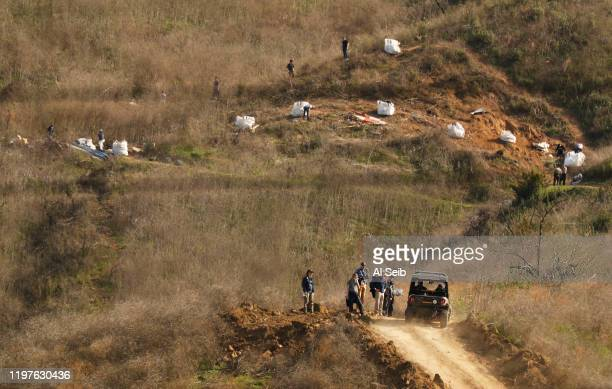Investigators walk down the bulldozed dirt road Tuesday morning after working at the hillside scene of the helicopter crash that killed Kobe Bryant...
