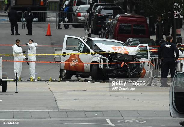 Investigators work around the wreckage of a Home Depot pickup truck a day after it was used in an terror attack in New York on November 1 2017 The...