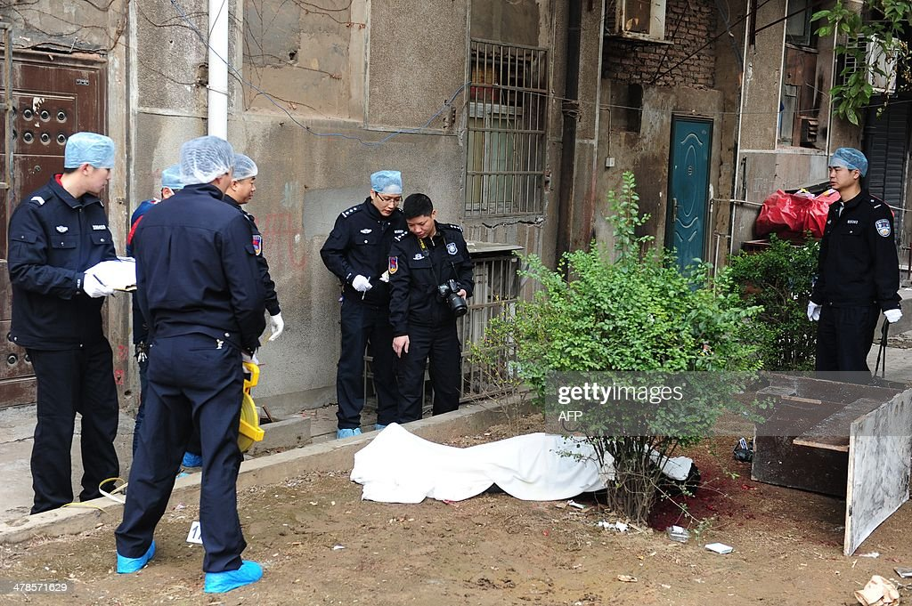 Investigators work at the crime scene near a victim's body (C) where attackers armed with knives killed three people in Changsha, central China's Hunan province on March 14, 2014. Attackers armed with knives killed three people in China on March 14, an official said, ruling out terrorism two weeks after a mass stabbing blamed on Xinjiang militants left 29 people dead and stunned the nation. CHINA