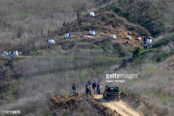 Investigators work at the scene of the helicopter crash, where former NBA star Kobe Bryant and his 13-year-old daughter Gianna died, on January 28,...