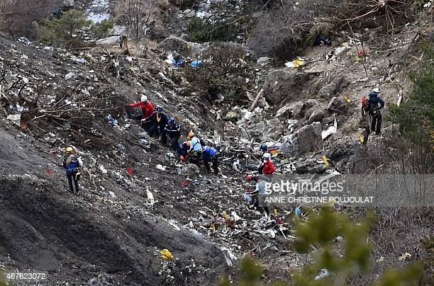 Investigators work on March 26 2015 near scattered debris while making their way through the crash site of the Germanwings Airbus A320 that crashed...