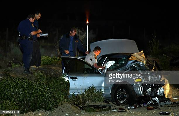 Investigators working at mangled remains of a Ford Crown Victoria in which two LAPD detectives were travelling tOne of the two LAPD detective was...